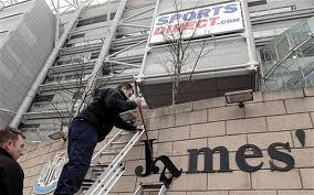 "Workmen removing the name ""St James' Park"" from the ground in February 2012"